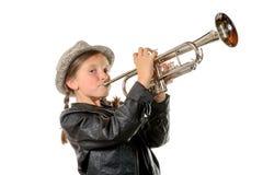 Una niña bonita con una chaqueta del negro toca la trompeta Foto de archivo libre de regalías