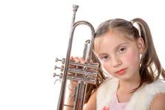 Una niña bonita con una mirada de la trompeta en la cámara Imagen de archivo libre de regalías