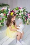 Una niña bonita en un vestido amarillo se sienta y juega con un juguete del conejo en un estudio Imagen de archivo