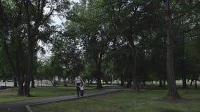 Una niña camina equilibrando en el encintado que lleva a cabo la mano de su madre metrajes
