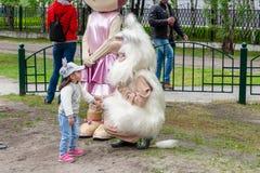 Una niña comunica con una muñeca de la estatura grande Buba el brownie foto de archivo