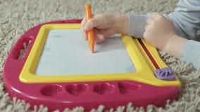 Una niña con el pelo ondulado rojo miente en el piso y dibuja en un tablero magnético El concepto del proceso educativo almacen de metraje de vídeo