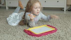Una niña con el pelo ondulado rojo miente en el piso y dibuja en un tablero magnético El concepto del proceso educativo almacen de video