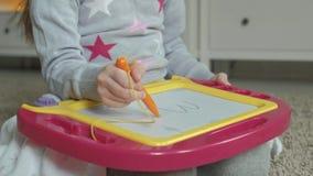 Una niña con el pelo ondulado rojo miente en el piso y dibuja en un tablero magnético El concepto del proceso educativo metrajes