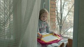 Una niña con el pelo ondulado rojo se sienta en el alféizar y dibuja en un tablero magnético El concepto del educativo almacen de metraje de vídeo