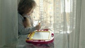 Una niña con el pelo ondulado rojo se sienta en el alféizar y dibuja en un tablero magnético El concepto del educativo metrajes