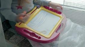 Una niña con el pelo ondulado rojo se sienta en el alféizar y dibuja en un tablero magnético El concepto del educativo almacen de video