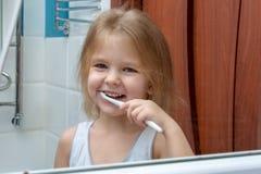 Una niña con el pelo rubio que cepilla sus dientes El niño está sonriendo en la reflexión en el espejo imagenes de archivo