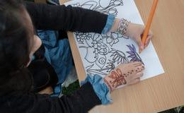 Una niña con el tatuaje de la alheña en sus flores que colorean de la mano en el papel foto de archivo