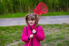 Una niña con la red de la mariposa que se divierte imagen de archivo