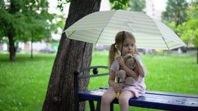 Una niña con una liebre del juguete se sienta en un banco debajo de un paraguas almacen de metraje de vídeo