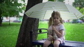 Una niña con una liebre del juguete se sienta en un banco debajo de un paraguas almacen de video