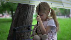 Una niña con una liebre del juguete se sienta en un banco debajo de un paraguas metrajes