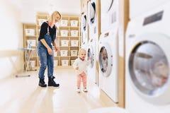 una niña con su madre lanza la ropa en el mach que se lava fotografía de archivo