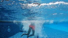 Una niña con un comienzo corriente que salta en la piscina y las nadadas debajo del agua almacen de metraje de vídeo