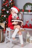 Una niña con un golden retriever del perrito en un fondo del árbol de navidad Foto de archivo libre de regalías