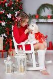 Una niña con un golden retriever del perrito en un fondo del árbol de navidad Imágenes de archivo libres de regalías