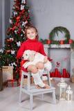 Una niña con un golden retriever del perrito en un fondo del árbol de navidad Imagen de archivo