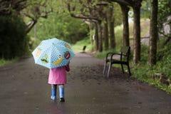 Una niña con un paraguas colorido imagenes de archivo