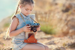 Una niña con una cámara vieja en una carretera nacional que se sienta en una maleta Imagenes de archivo