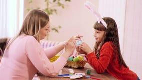 Una niña del aspecto caucásico con los oídos del conejito en la cabeza celebra el huevo, y a su madre con un cepillo y con metrajes
