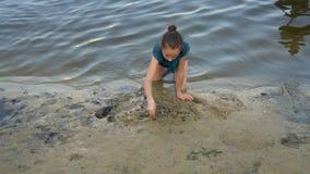 Una niña dibuja un corazón en la arena mojada en el borde del agua en la puesta del sol, sentándose en sus rodillas La visi?n des almacen de metraje de vídeo