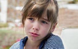 Una niña dulce puso mala cara y lloró, ofendido, un capricho infantil Imagenes de archivo