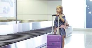 Una niña dulce tomó una maleta púrpura del carrusel de la demanda de equipaje almacen de video
