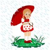 Una niña en la lluvia con un paraguas Imágenes de archivo libres de regalías