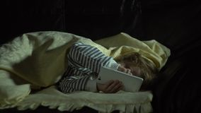 Una niña en los pijamas rayados en la noche en su sitio utiliza un smartphone almacen de metraje de vídeo