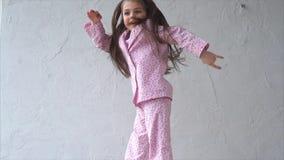 Una niña en pijamas salta en la cama en el dormitorio, aumentando sus manos para arriba almacen de video