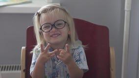 Una niña en pijamas y vidrios azules almacen de metraje de vídeo