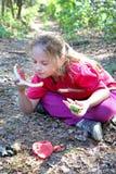 Una niña en ropa rosada come la sentada de la sandía en hierba seca imagenes de archivo