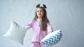 Una niña en sus pijamas hechos en casa pone las almohadas, ella el ` s que se divierte metrajes