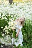 Una niña en un campo de la manzanilla fotografía de archivo