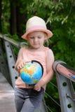 Una niña en un sombrero de paja está sosteniendo un globo en sus manos El niño considera el modelo del globo fotos de archivo
