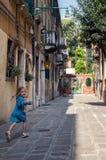 Una niña en un vestido azul corre a lo largo de una calle veneciana vieja y de risas feliz fotografía de archivo