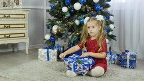 Una niña en un vestido azul desempaqueta un regalo del ` s del Año Nuevo debajo de un árbol de navidad Fotografía de archivo libre de regalías
