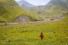 Una niña en un vestido rojo y una casquillo-fresa hecha punto corre en un campo verde en las montañas foto de archivo