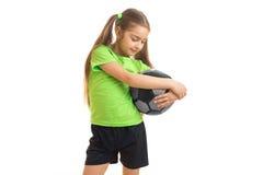 Una niña en una camiseta brillante se coloca en el estudio y abraza las manos de la bola Imagenes de archivo