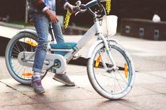 Una niña en vaqueros desiguales se sienta en una pequeña bicicleta blanca blanca con blanco rueda adentro el parque imagenes de archivo