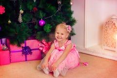Una niña en vestido rosado en la Navidad Imagen de archivo