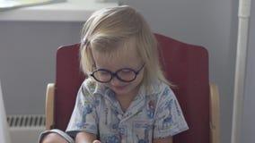 Una niña en vidrios y pijamas se está sentando en la tabla de cocina metrajes