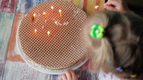 Una niña enciende velas en una torta hecha en casa El concepto de autonomía metrajes