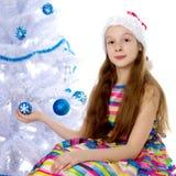 Una niña está adornando un árbol de navidad Imágenes de archivo libres de regalías