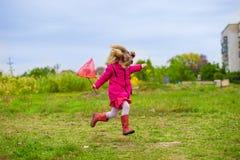 Una niña está corriendo con la red de la mariposa que se divierte fotografía de archivo libre de regalías
