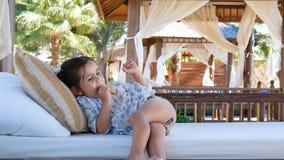 Una niña está descansando sobre los asientos suaves del gazebo almacen de metraje de vídeo
