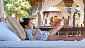 Una niña está descansando sobre los asientos suaves del gazebo metrajes