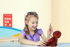 Una niña está jugando al doctor - ella está examinando un oso del juguete imagen de archivo