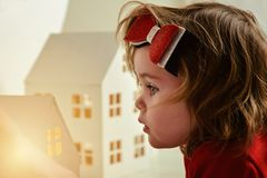 Una niña está jugando con una pequeña casa fabulosa del juguete foto de archivo libre de regalías